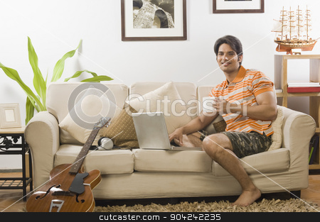 pims_20090401_sh0271.jpg stock photo, Young man holding a coffee mug in the living room by imagedb