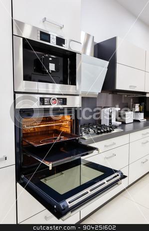 Modern custom hi-tek kitchen, oven with open door stock photo, Modern luxury custom hi-tek black and white kitchen, clean interior design, focus at oven with open door by Serghei Starus