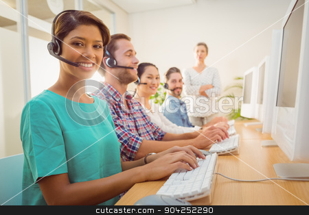 Call center agent working under a manager supervision  stock photo, Portrait of pretty call center agent working under a manager supervision  by Wavebreak Media