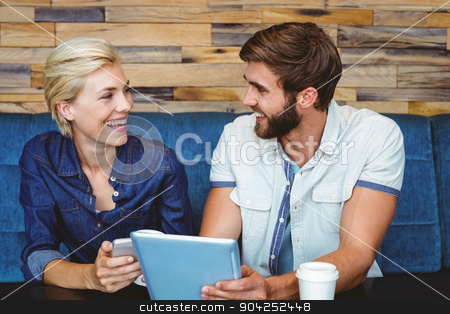 Cute couple on a date watching photos on a tablet stock photo, Cute couple on a date watching photos on a tablet at the cafe by Wavebreak Media