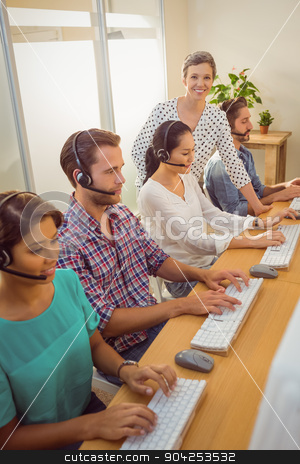 Manager assisting staffs in call center stock photo, Portrait of female manager assisting staffs in a call center by Wavebreak Media