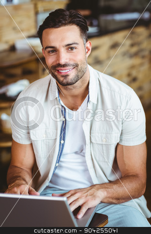 Happy young businessman working at laptop drinking coffee stock photo, Happy young businessman working at laptop drinking coffee at coffee shop by Wavebreak Media