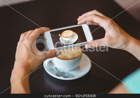 Woman taking picture with her smartphone  stock photo, Woman taking picture with her smartphone at the cafe  by Wavebreak Media
