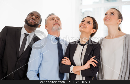 Concept for multi-ethnic business team stock photo, Multi-ethnic business team standing in office, smiling and looking up by Dmytro Sidelnikov