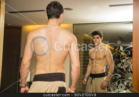Young Man Admiring His Muscles in Mirror stock photo, Young Shirtless Handsome Muscular Man Admiring His Muscles in Gym Mirror or Checking Progress and Training Results, as seen from Behind by Stefano Cavoretto