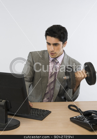 pims_20091020_as0588.JPG stock photo, Businessman exercising with dumbbells and working on a computer by imagedb