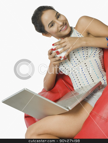 pims_20091109_rc0113.JPG stock photo, Woman using a laptop with a cup of coffee by imagedb