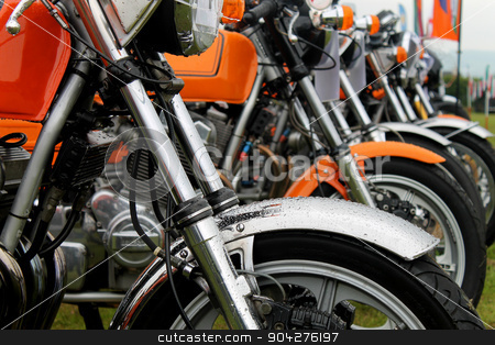 Row of motorbikes stock photo, Row of motorbikes in a field by Martin Crowdy