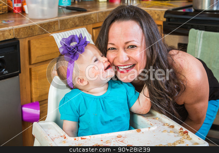 Baby Kisses Mother stock photo, Baby girl gives her mother a kiss in the kitchen by Scott Griessel