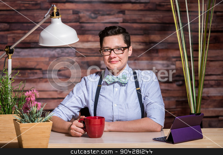 Dapper Woman in Stylish Office at Wood Desk with Mug stock photo, Dapper woman at stylish office desk with a red coffee mug by Scott Griessel