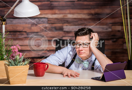Disappointed Businesswoman at Desk stock photo, Disappointed lesbian businesswoman leaning against arm at desk by Scott Griessel