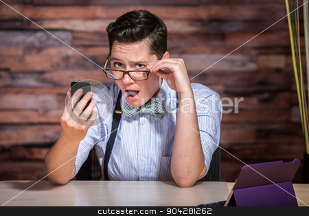 Insulted Boyish Woman Looking at Phone stock photo, Insulted boyish woman holding eyeglasses and looking at phone by Scott Griessel