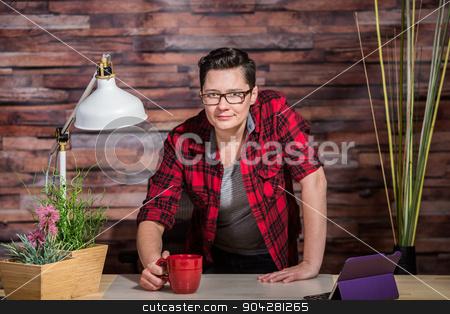 Woman Standing Behind Desk stock photo, Boyish casual businesswoman standing behind desk by Scott Griessel