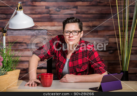 Suspicious Woman at Desk stock photo, Woman in flannel shirt leaning on modern desk with red cup by Scott Griessel