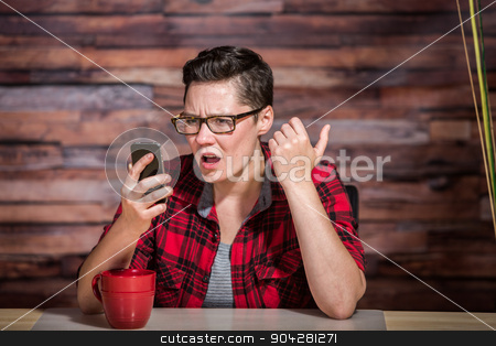 Shocked Butch Woman with Phone stock photo, Serious woman wearing flannel shirt looking at smart phone and seated in front of modern desk at hipster office by Scott Griessel