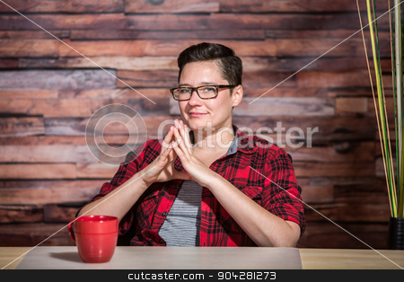 Crafty Boyish Businesswoman stock photo, Crafty boyish businesswoman with eyeglasses at desk with mug by Scott Griessel
