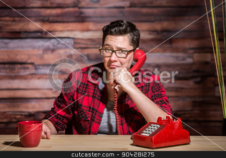 Frowning Woman on Red Phone stock photo, Frowning woman on red phone in hipster office by Scott Griessel