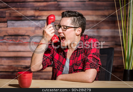 Young Woman Screams Into Phone stock photo, A young professional woman screams into red phone by Scott Griessel