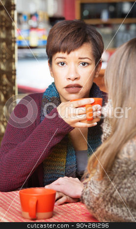Sympathetic Woman with Friend stock photo, Sympathetic woman with friend at coffee house indoors by Scott Griessel