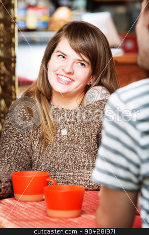 Cute Woman Smiling at Friend stock photo, Cute woman smiling at friend in restaurant by Scott Griessel