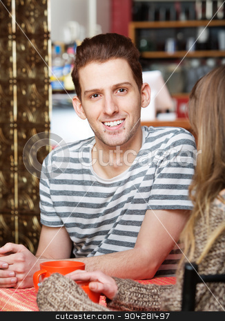 Handsome Man Sitting with Friend stock photo, Handsome Caucasian male sitting at table with friend by Scott Griessel