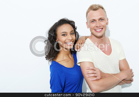 Sweet couple isolated on white stock photo, Mixed couple. Beautiful young mulatto girl standing holding her arm at the shoulder of blond boyfriend looking happy, both smiling, isolated on white background by Viacheslav Iakobchuk