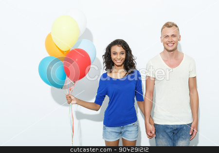 Sweet couple isolated on white stock photo, Mixed couple. Portrait of a blond young man standing and holding hand of his pretty mulatto girlfriend holding colorful balloons smiling happily, isolated on white background by Viacheslav Iakobchuk