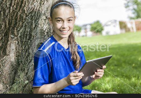 Teenager girl using a tablet wearing in soccer sport stock photo, A teenager girl using a tablet wearing in soccer sport by Louis-Paul St-Onge