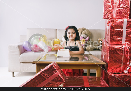 Portrait of a girl standing in front of a cake and smiling stock photo, Portrait of a girl standing in front of a cake and smiling by imagedb