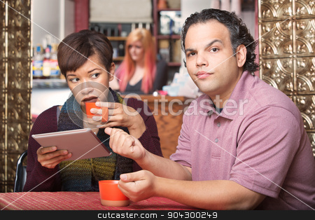 Hispanic Woman Ignoring Boyfriend stock photo, Pretty Hispanic woman reading tablet and ignoring boyfriend by Scott Griessel