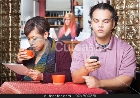 Distracted Couple Using Devices stock photo, Young distracted African American couple using digital devices in cafe by Scott Griessel