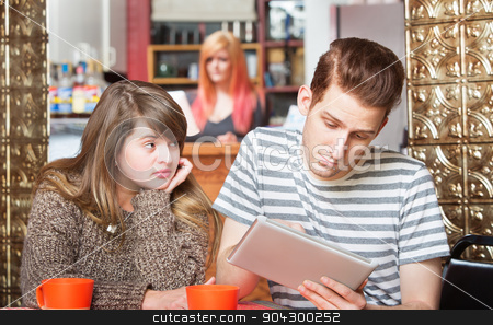 Hopeful Woman Looking at Distracted Boyfriend stock photo, Sad woman looking over at boyfriend using computer tablet by Scott Griessel