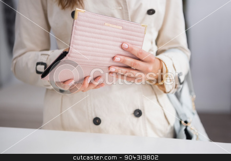 Woman opening her wallet stock photo, Woman opening her wallet at a boutique by Wavebreak Media