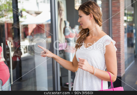 Smiling Woman with shopping bag pointing the window stock photo, Smiling Woman with shopping bag pointing the window at the shopping mall by Wavebreak Media