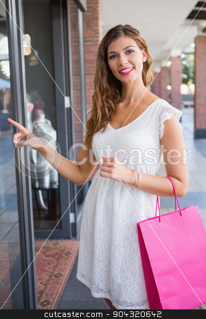 Portrait of smiling woman pointing the window and looking at cam stock photo, Portrait of smiling woman pointing the window and looking at camera at the shopping mall by Wavebreak Media