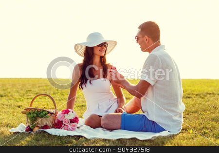smiling couple with small red gift box on picnic stock photo, love, dating, people and holidays concept - smiling young man showing small red gift box to his girlfriend on picnic by Syda Productions