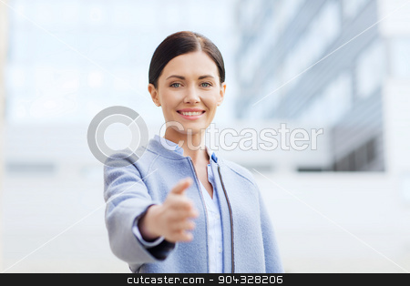 smiling businesswoman giving hand for handshake stock photo, business, partnership, cooperation and people concept - young smiling businesswoman giving hand for handshake over office building by Syda Productions