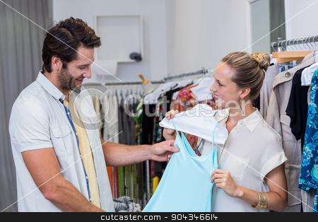 Smiling woman showing dress to boyfriend stock photo, Smiling woman showing dress to boyfriend in clothing store by Wavebreak Media