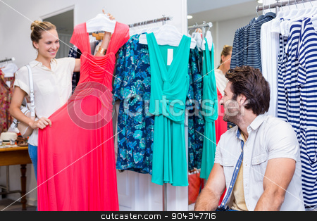 Smiling woman showing red dress to boyfriend stock photo, Smiling woman showing red dress to boyfriend in clothing store by Wavebreak Media