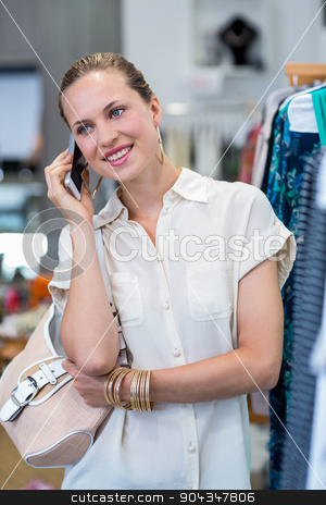 Smiling woman phoning next to clothes rail stock photo, Smiling woman phoning next to clothes rail in clothing store by Wavebreak Media