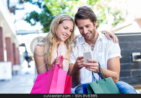 Smiling couple with shopping bags sitting and using smartphone stock photo, Smiling couple with shopping bags sitting and using smartphone at shopping mall by Wavebreak Media