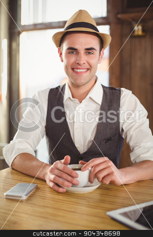 Smiling hipster with cup of coffee stock photo, Portrait of smiling hipster with cup of coffee at coffee shop  by Wavebreak Media