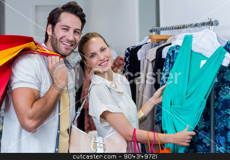Smiling couple browsing clothes stock photo, Portrait of smiling couple browsing clothes in clothing store by Wavebreak Media