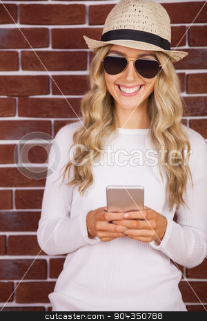 Gorgeous blonde hipster with sunglasses using smartphone stock photo, Gorgeous blonde hipster with sunglasses using smartphone against red brick background by Wavebreak Media