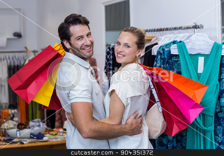 Smiling couple with shopping bags embracing stock photo, Portrait of smiling couple with shopping bags embracing in clothing store by Wavebreak Media