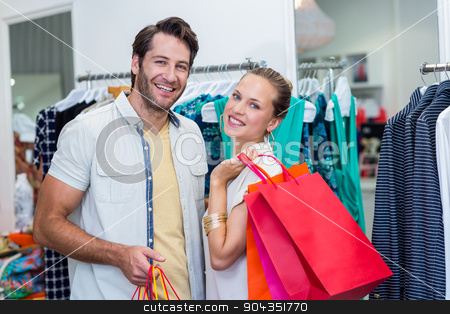 Smiling couple with shopping bags  stock photo, Portrait of smiling couple with shopping bags in clothing store by Wavebreak Media