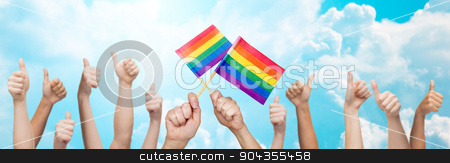 hands showing thumbs up and holding rainbow flags stock photo, people, gay pride, gesture and homosexual concept - human hands showing thumbs up and holding rainbow flags over blue sky background by Syda Productions
