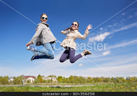 happy little girls jumping high outdoors stock photo, people, children, friends and friendship concept - happy little girls jumping high outdoors by Syda Productions