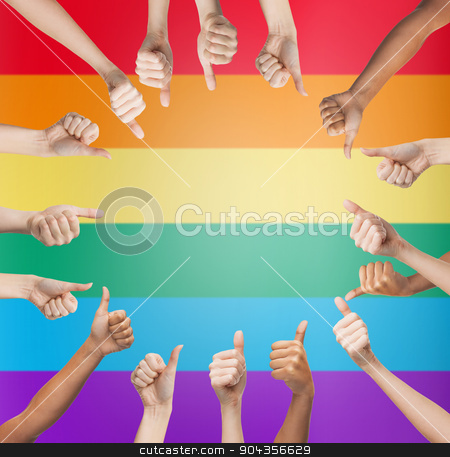 hands showing thumbs up in circle over rainbow stock photo, people, gay pride, gesture and homosexual concept - human hands showing thumbs up in circle over rainbow flag stripes background by Syda Productions