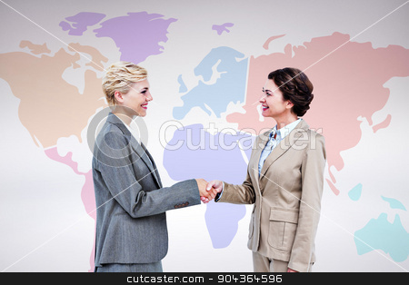 Composite image of  smiling women shaking hands stock photo,  Smiling women shaking hands against grey background by Wavebreak Media